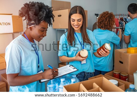 Group of people working in charitable foundation. Happy volunteer looking at donation box on a sunny day. Happy volunteer separating donations stuffs. Volunteers sort donations during food drive
