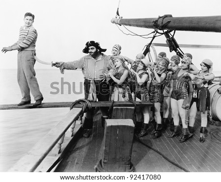 Group of pirates trying to push a young man over a plank
