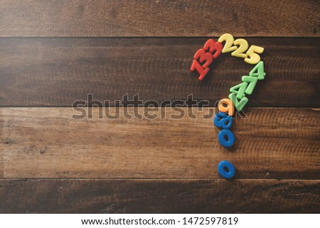 Group of plastic toy numbers forming question mark on a wooden table. Concept of Questions, faq and mathematical problems