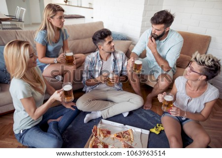 Group of playful young people eating pizza while having fun together. #1063963514