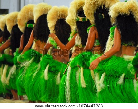 Group of Polynesian dancers in traditional green dresses performing in Raiatea, French Polynesia