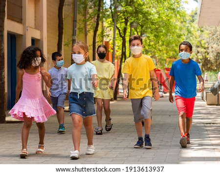 Group of positive children in masks walking together on the street Foto stock ©