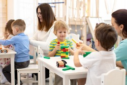 Group of preschool children and teacher playing with building blocks together in kindergarten