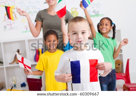 group of preschool kids and teacher with flags in classroom - stock photo