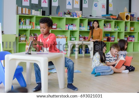 Group Of Preschool Kids In Attention Playing And Learning Classroom With Teacher Watching Closely