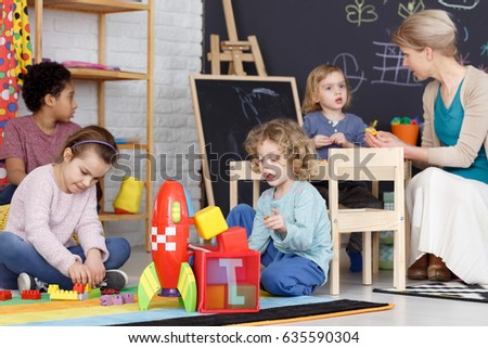 Group of preschool kids playing with toys on a carpet