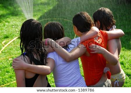 Group of preteen girls having fun outside running through sprinkler ...