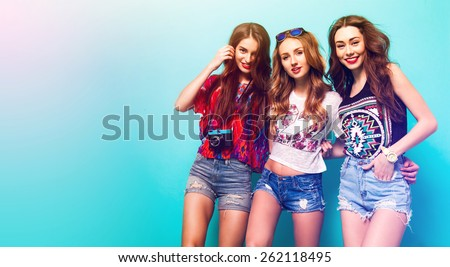 Group of pretty young girls in stylish clothes posing in studio against blue background. Three pretty  woman smiling  and wolfing together. sunny summer colors.  #262118495