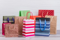Group of printed paper shopping bags. Assortment of paper carrier bags with printing, horizontal image. Sale, consumerism, advertisement and retail.