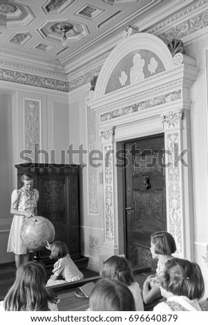 Group of pupils and girl pointing at globe in classroom #696640879