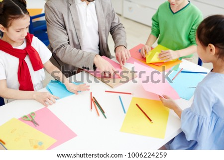 Group of pupils and their teacher making origami from colorful paper at lesson #1006224259