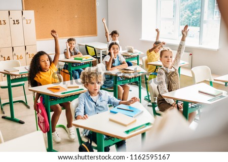 group of pupils raising hands to answer question during lesson at classroom