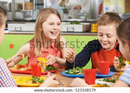Group Of Pupils Sitting At Table In School Cafeteria Eating Lunch