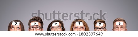 Group of puzzled young people with paper stickers with question mark on foreheads looking up while playing Who Am I game on gray background