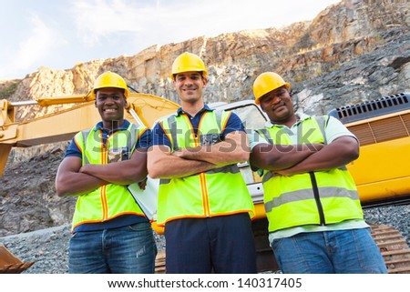group of quarry workers standing next to excavator with arms crossed