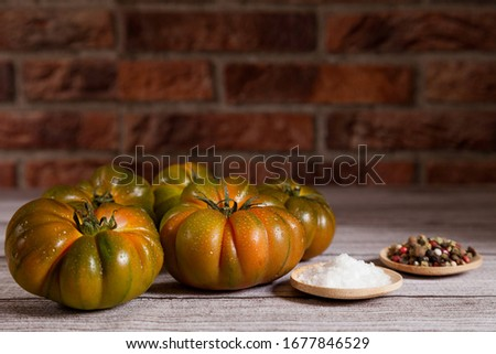 Group of raf tomatoes with salt and peppercorns on wooden table and brick background. Copy space Zdjęcia stock ©