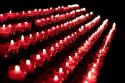 Group of red candles in church for faith resurrection prayer. Candlelight fire flames in rows are silent religion symbol for peace, life and soul. Obituary hope sacrifice against sorrows and pain