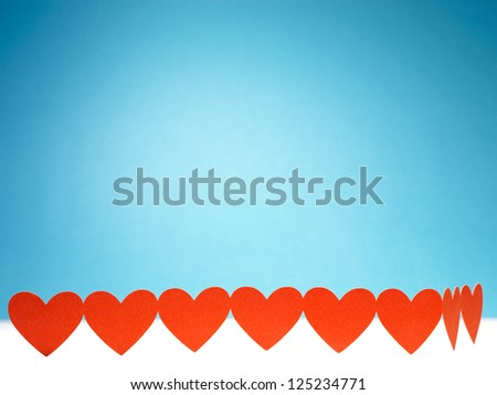 Group of red valentine hearts connected in chain on blue background - stock photo