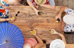 Group of relaxed people drinking cocktails at wooden table. Male female hands keeping varied drinks dressed resort style summer huts grunge natural handcrafted desk sun umbrella located cafe terrace