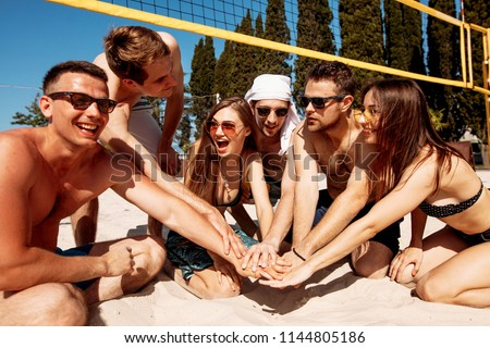Group of relaxing smiling friends in beach outfit sitting on sand forming a circle, people hands, stacked huddle together- Team people, friendship concept