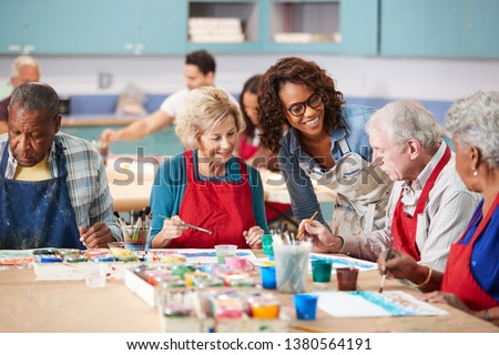 Group Of Retired Seniors Attending Art Class In Community Centre With Teacher