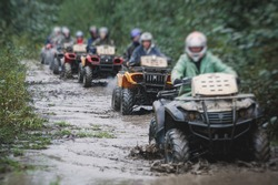 Group of riders riding atv vehicle on off road track, process of driving ATV vehicle, all terrain quad bike vehicle, during offroad competition, crossing a puddle of mud