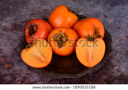 Group of Ripe orange persimmon fruit.Persimmon fruits in plate, rustic background, Hurma fruit
