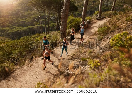 Group of runners in a cross country race. Young people running in nature. Trail running workout.