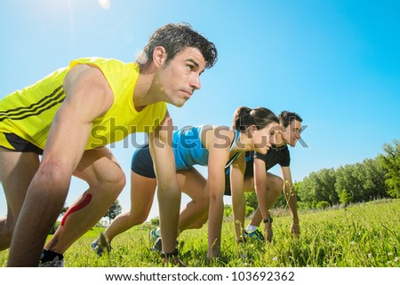 Group of runners ready for running challenge outdoors. Young athetes at the starting line ready to sprint and sport. Copyspace.