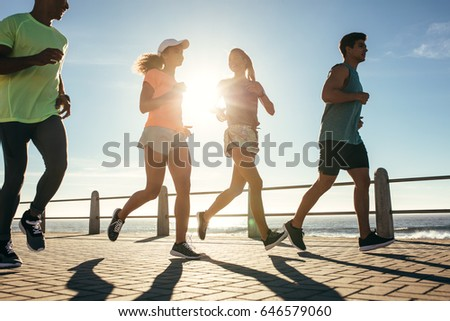Group of runners running on road by the seaside on a sunny day. Healthy young people training together outdoors.