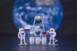Group of russian vaccines named after a well-known russian satellite against Covid 19 virus with a group of small astronauts. Out of focus. Tag text reads, corona virus injection only.