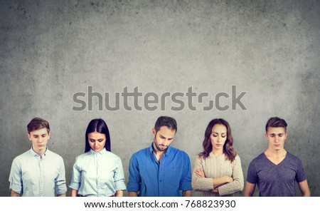 Group of sad unhappy people men and women standing against gray wall looking down. Negative human emotions