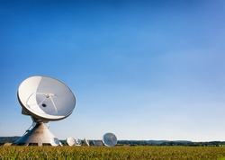 group of satelite dishes in front of blue sky