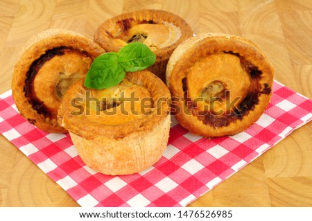 Group of savoury crusty pork pies on a paper gingham pattern napkin with a wood background