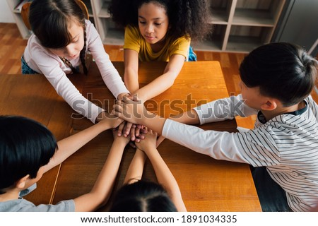 Group of school friends with hands stacked one on top of another, friendship, support, togetherness. Multiethnic school children with hands touching on top of each other Stock foto ©