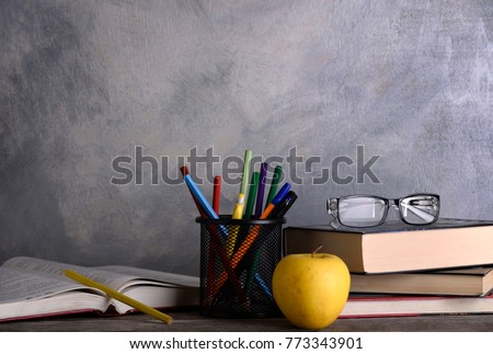 Group of school supplies and books on wooden table over a grey background  #773343901