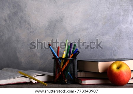 Group of school supplies and books on wooden table over a grey background  #773343907