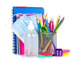 Group of school supplies and COVID 19 prevention items isolated on a white background. Back to school during pandemic con