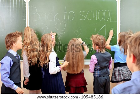 Group of schoolchildren writing on a blackboard at a classroom. Education.