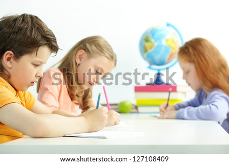 Group of schoolmates drawing at lesson