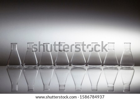 Group of scientific laboratory glass erlenmeyer flask glassware equipment on reflective surface.