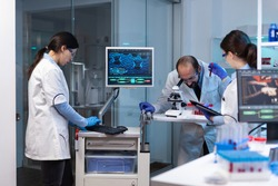 Group of scientists doing research and experiments at medical lab against disease with special equipment. Doctors specialists doing scientific experiment and searching medical treatment