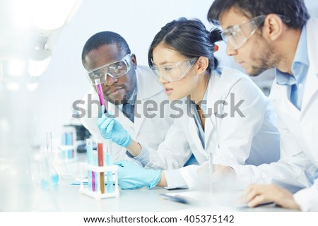 Group of scientists studying reaction of some chemical