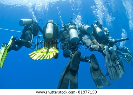 Group of scuba divers at a decompression safety stop on rope underwater