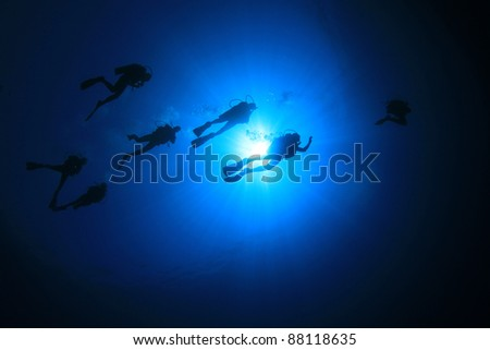 Group of Scuba Divers in the Sea, silhouettes against Sunburst