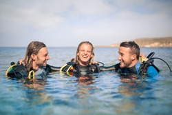 Group of scuba divers laughing together in the sea
