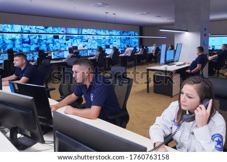 Group of Security data center operators working in a CCTV monitoring room looking on multiple monitors  Officers Monitoring Multiple Screens for Suspicious Activities  Team working on the System Contr Photo stock ©