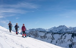 group of 3 senior adults snowshoeing  in the Bregenz wald mountains above the village of Bezau, Vorarlberg, Austria