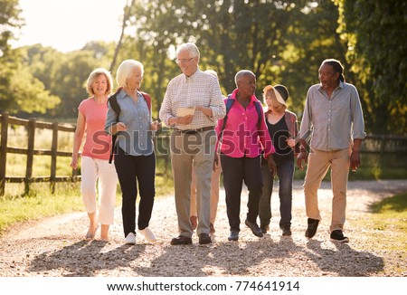 Group Of Senior Friends Hiking In Countryside