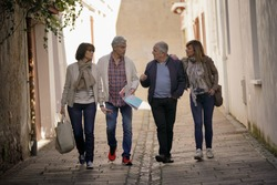 Group of senior friends walking in street of French town